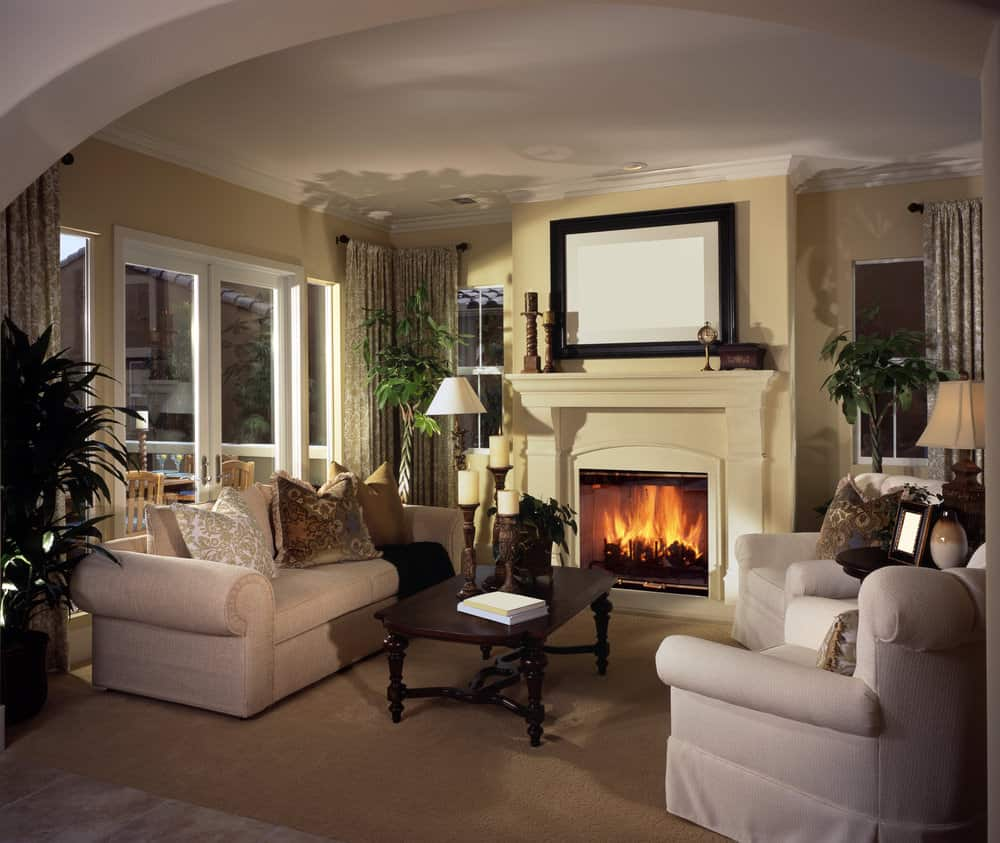 This formal living room features a classy fireplace and a set of comfy seats with a center table.