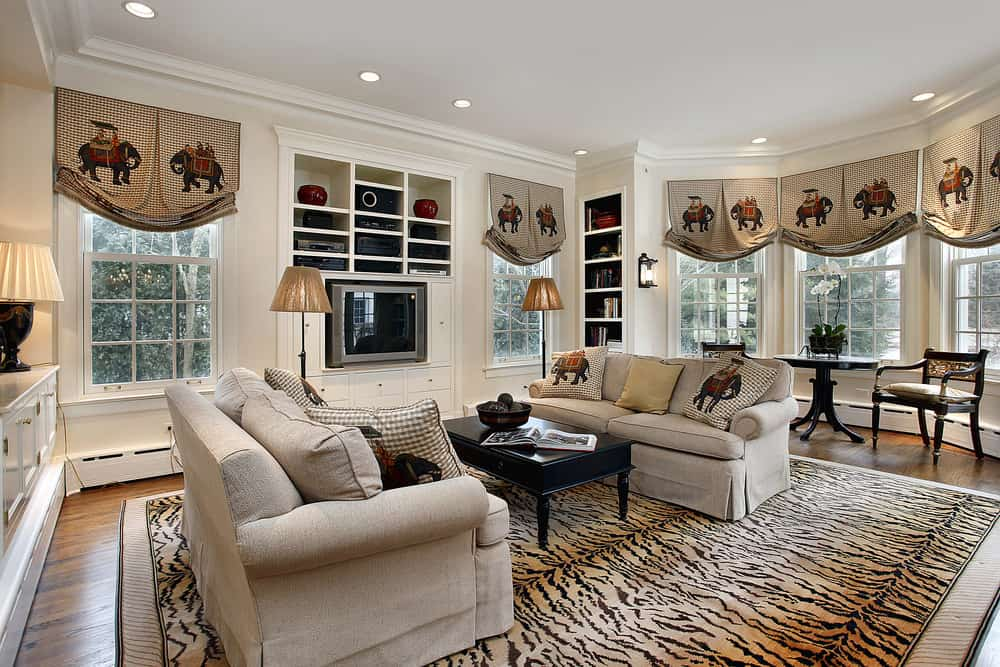 Huge family room featuring a pair of couches and a classy center table set on a tiger-printed area rug covering the hardwood flooring.