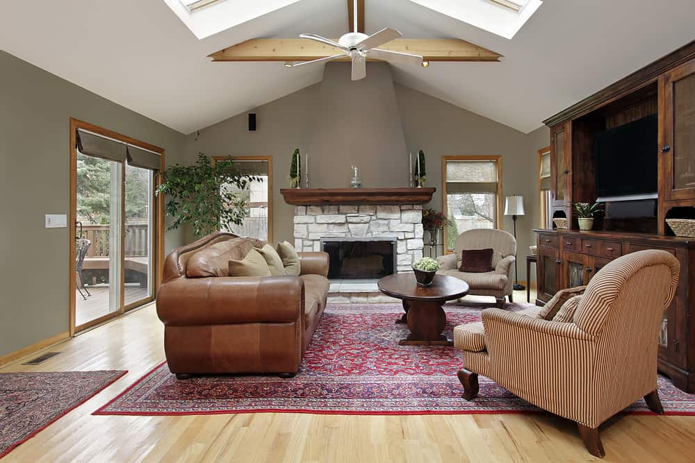 A spacious family living space featuring a large and luxurious-looking brown leather couch set in front of the TV. There's a stone fireplace on the side. The room also has skylights.