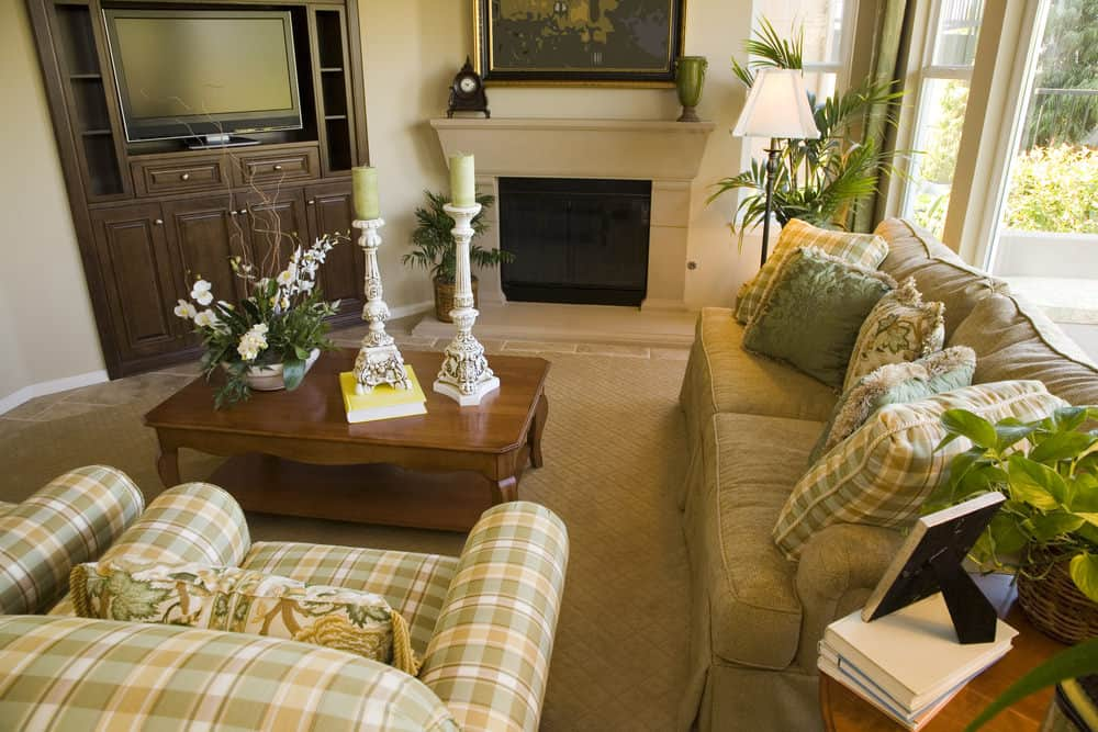 A close up look at this formal living room's classy seats and a wooden center table set near the home's fireplace.