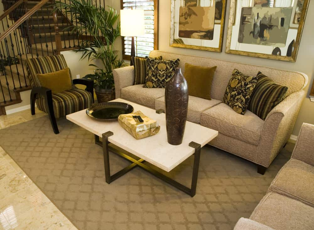 A focused shot at this Country-style formal living room's elegant seats and a stylish center table set on top of an area rug covering the tiles flooring.