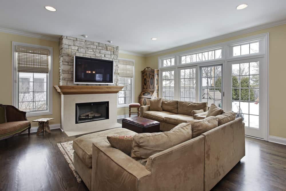 A spacious family living room with a cozy sofa set, a fireplace and a large widescreen TV on the wall.