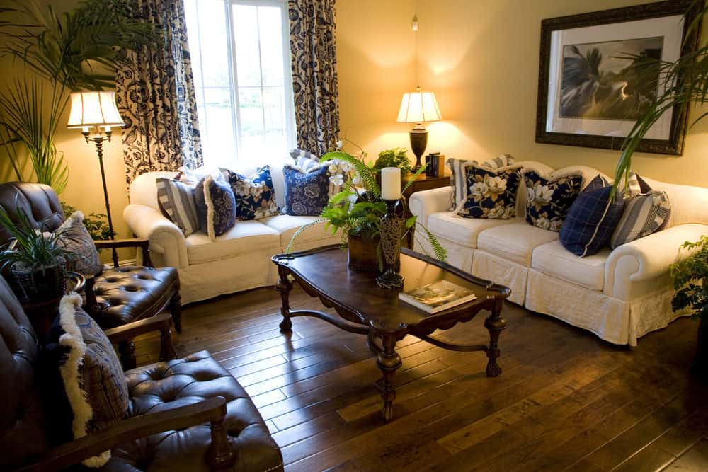 Country-style living room boasting a set of elegant seats and a classy center table set on the room's hardwood flooring and is surrounded by yellow walls.
