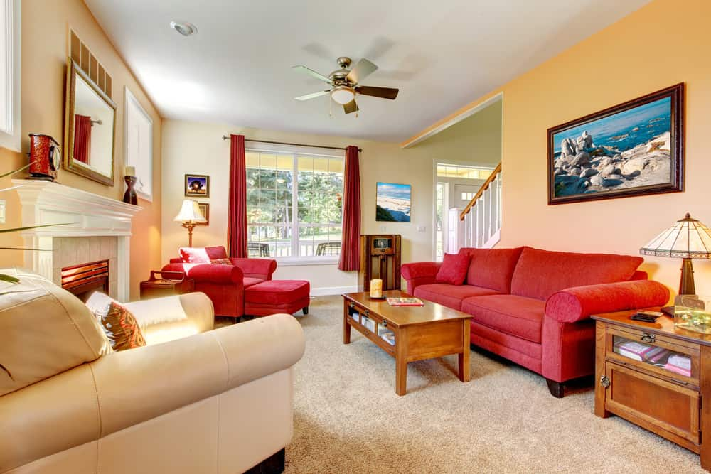 A large formal living room with a red couch and a red comfy chair with a matching footrest on the side. The area also has a fireplace and carpeted flooring.