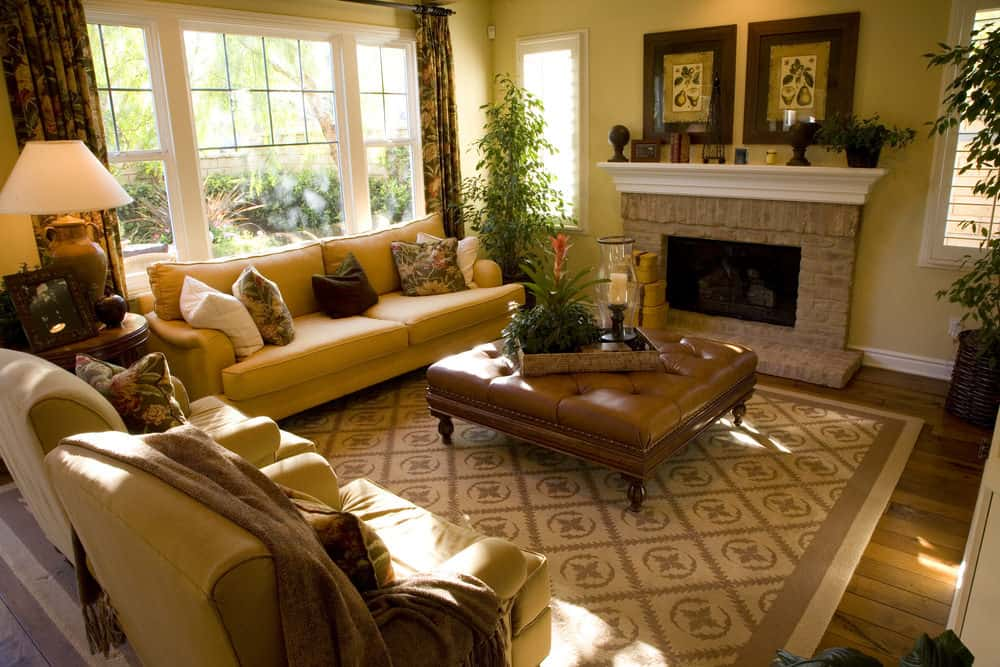 Country-style formal living room with hardwood floors and yellow walls. It offers a nice sofa set and a large ottoman in the middle, set near the fireplace.