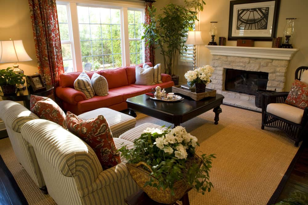 Large Country-style formal living room featuring a cozy sofa set along with a classy center table and a fireplace. The area is surrounded by multiple indoor plants.