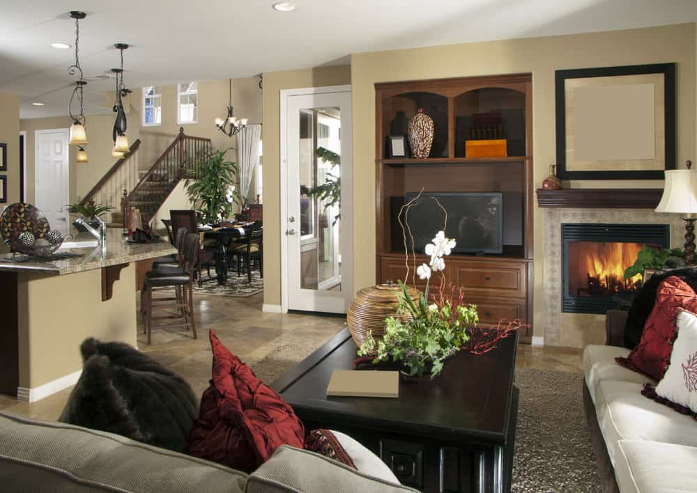 A great room with a family living space featuring a fireplace and a widescreen TV. The area has a large center table set on a gray area rug covering the tiles flooring.