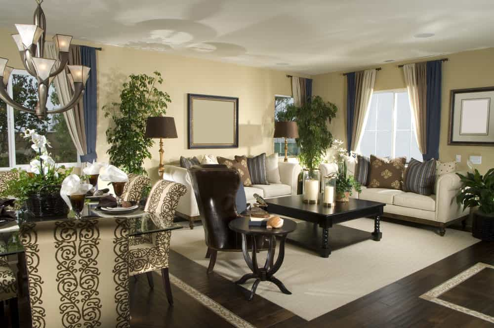 This great room features a classy sofa set in the living room, with a center table set on top of the area rug covering the hardwood flooring. The dining table set features elegantly designed seats and a glass top dining table.