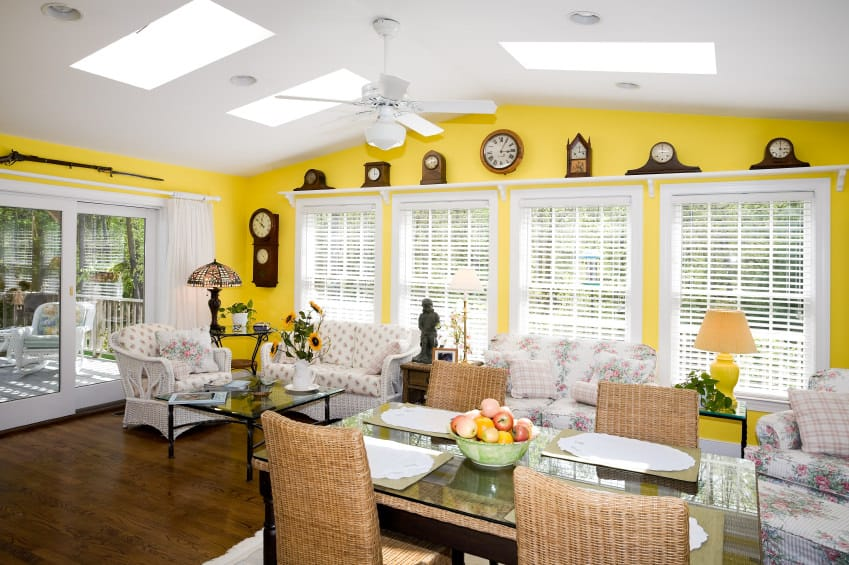 A spacious living Country-style living space surrounded by yellow walls and has a white ceiling with skylights and hardwood flooring. The room offers beautiful seats and a glass top small dining table set.