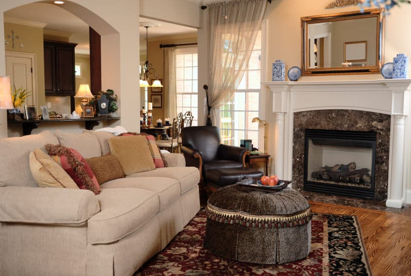 A focused look at this formal living room's cozy sofa set and a stylish ottoman, along with a gorgeous fireplace.