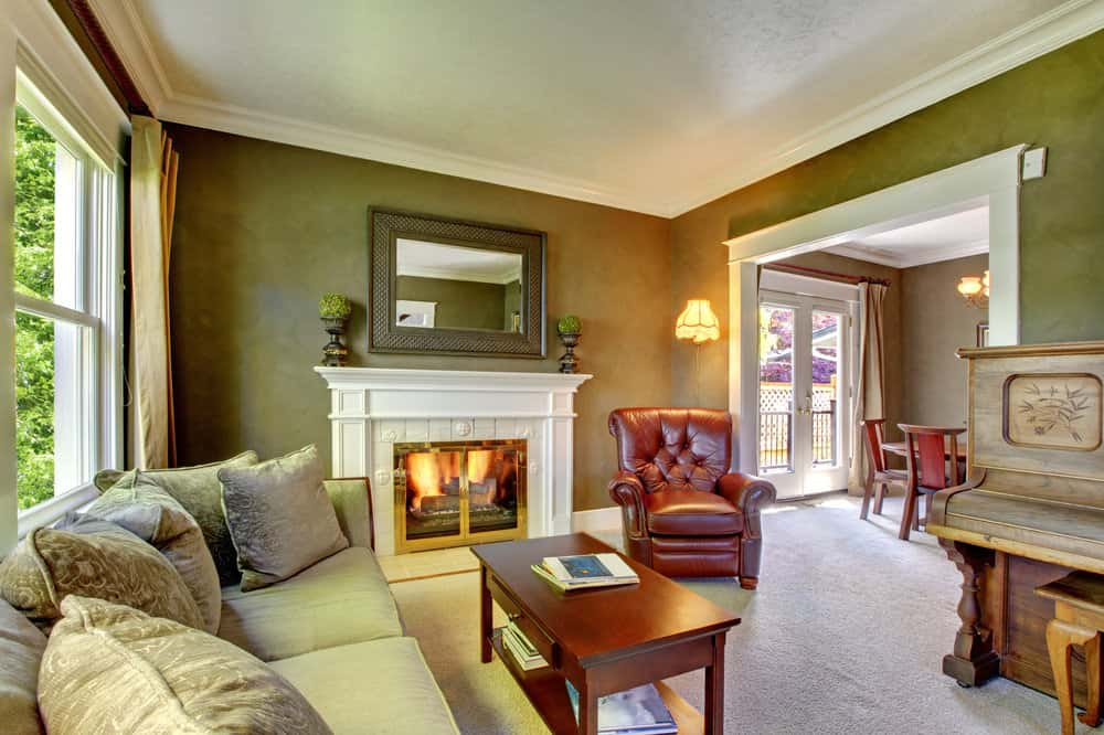 A formal living room boasting a large classy sofa set and a fireplace, along with a stunning vintage piano on the side.