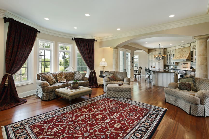 A spacious living room featuring elegant seats and a large stylish area rug covering the hardwood flooring. The window curtains add elegance to the area as well.