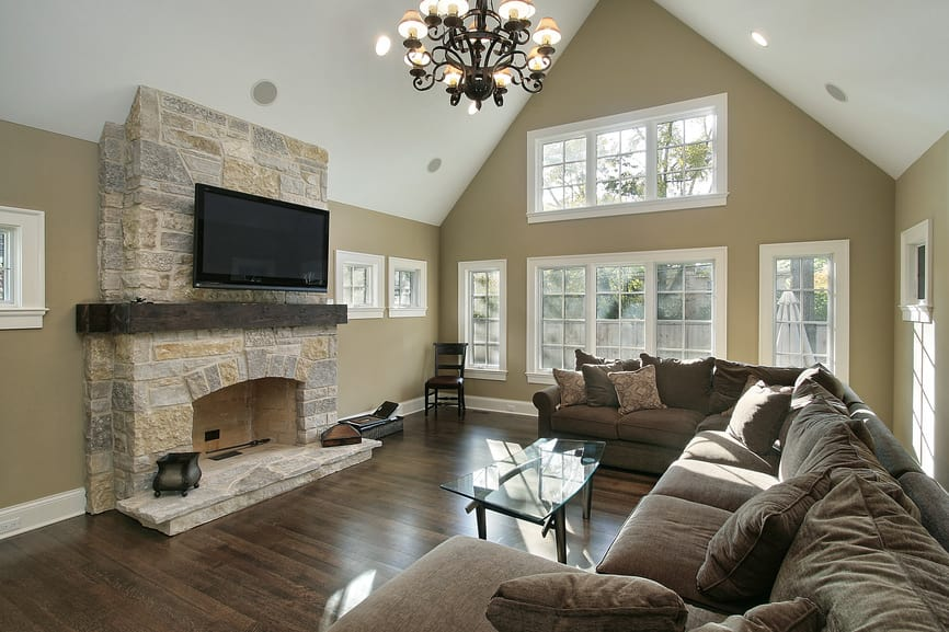 Large living room with a brown comfy sofa set and a large fireplace, with a large widescreen TV above it. The room is surrounded by brown walls and a tall vaulted ceiling.