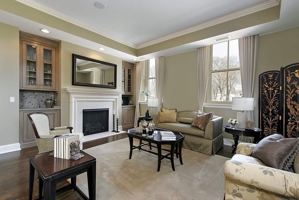 A spacious formal living room with a fireplace and a nice set of seats, together with matching center and side tables.