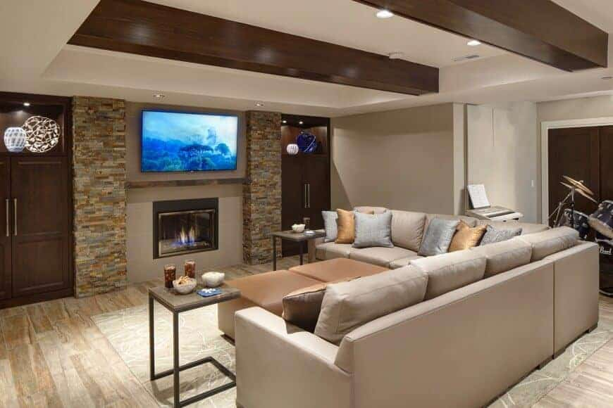 An L-shaped sofa faces the glass-enclosed fireplace with a wall mount TV on top. It is flank by brick columns and dark wood cabinets illuminated by recessed lights.