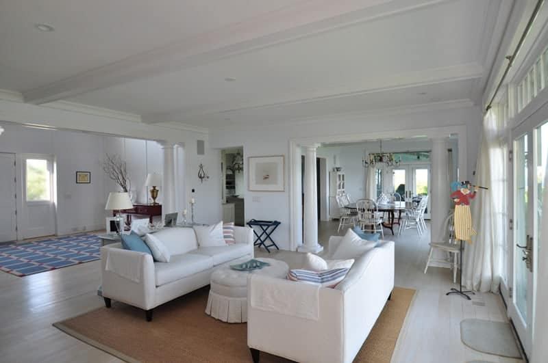 An open living room with a skirted ottoman and facing sofas blending in with the white walls and ceiling. It includes a brown area rug that lays on the wide plank flooring.