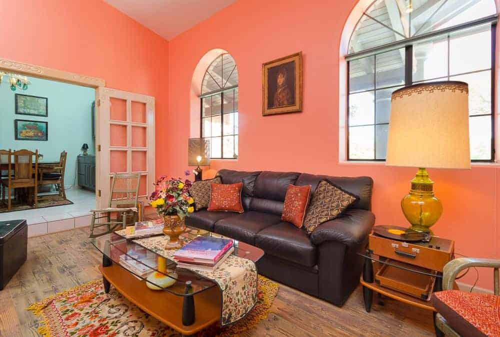 The pink living room showcases a glass top coffee table and a black leather sofa illuminated by oversized table lamps. It has arched windows and hardwood flooring topped by a tasseled rug.