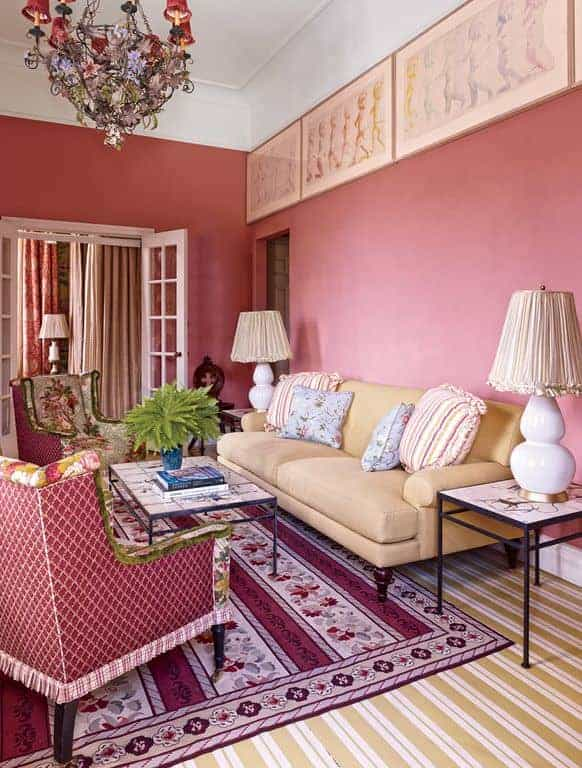 Gorgeous living room decorated with a series of framed wall arts along with a floral chandelier that hung over the metal coffee table. It has a beige sofa and red wingback chairs that sit on a striped rug over yellow carpet.