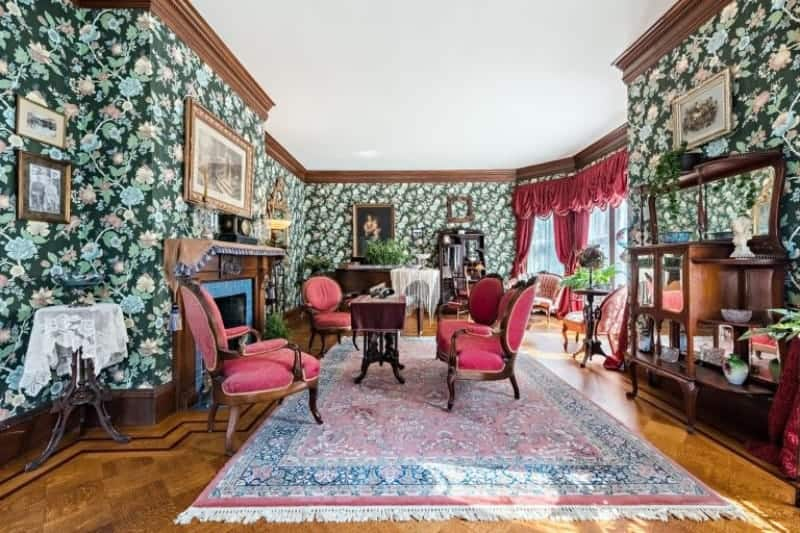 Victorian living room clad in green floral wallpaper that's filled with framed photos. It has a fireplace and red armchairs surrounding a wooden coffee table over a tasseled area rug.