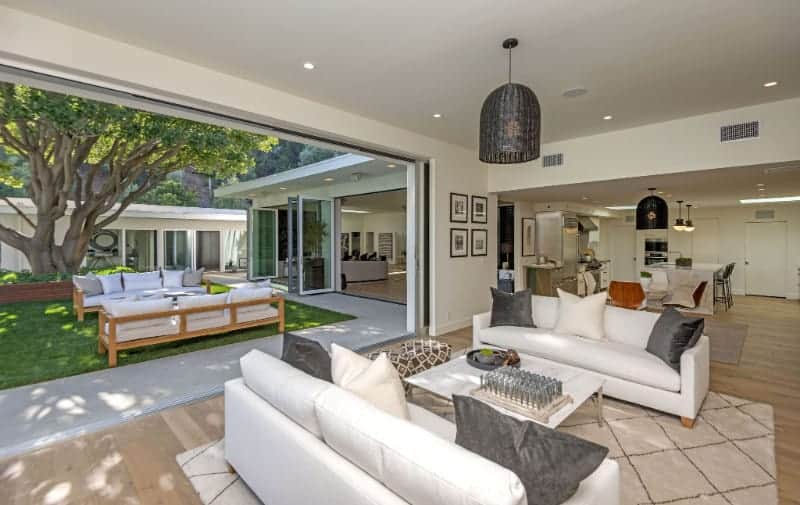 A medium-sized living room boasts white sofas and a marble coffee table lighted by an oversized dome pendant. It has wide plank flooring and a panoramic window overlooking the outdoor greenery which brings a serene ambiance to the room.