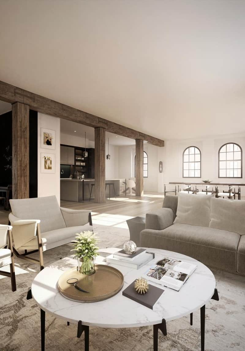 An expansive living room lined with wooden beam and columns offers beige armchairs and a gray sofa paired with a round marble coffee table over a printed area rug.