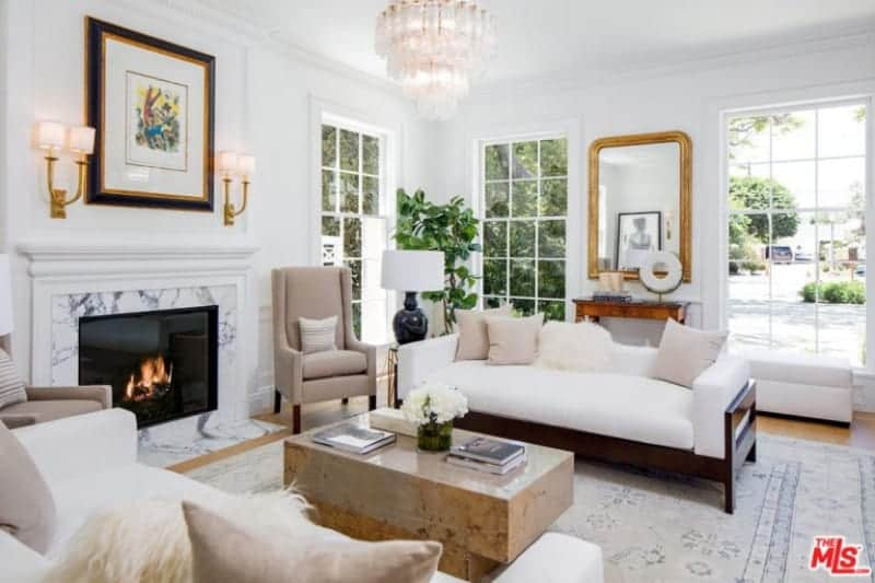 A fancy chandelier illuminates the sleek coffee table situated in between the white sofas filled with neutral and white faux fur pillows. It is accompanied by beige chairs and a fireplace framed in marble surround tiles and white mantel.