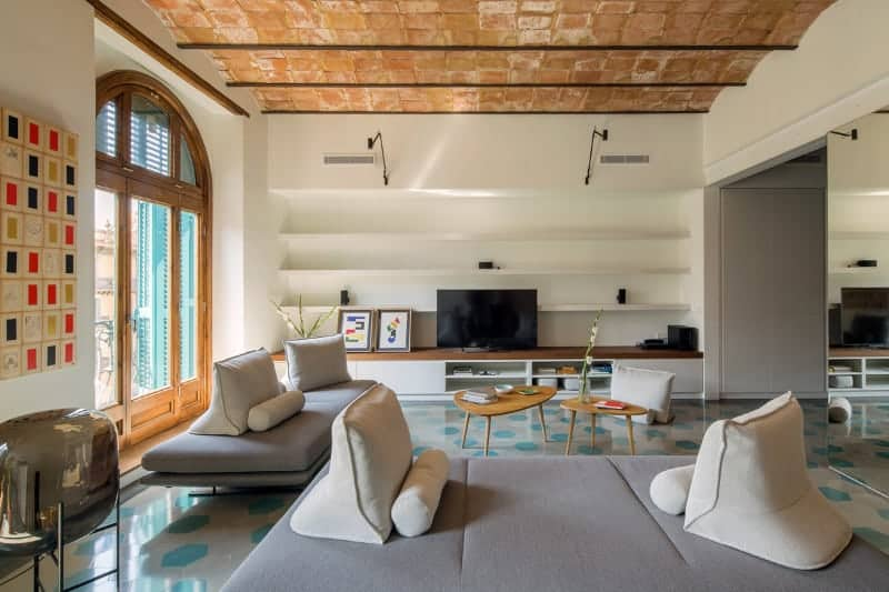 The sleek living room showcases an arched window and barrel vaulted ceiling clad in bricks. It has modern seats and wooden coffee tables facing the TV against the open shelving.