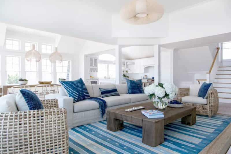 Beach style living room with a striped area rug and a rustic coffee table surrounded by gray seats that are accented with blue pillows. It is illuminated by a round chandelier along with natural light from the white framed windows.