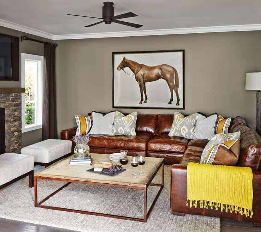 A horse painting hangs above the brown leather sofa filled with gray pillows and a yellow throw blanket. It is accompanied by a wooden coffee table and cushioned sits across the fireplace.