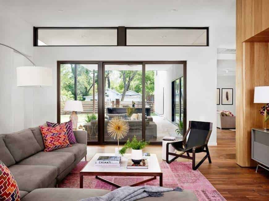 The medium-sized living room features a black chair and gray sectional accented with eye-catching pillows. It includes a wooden coffee table that sits on a pink area rug.