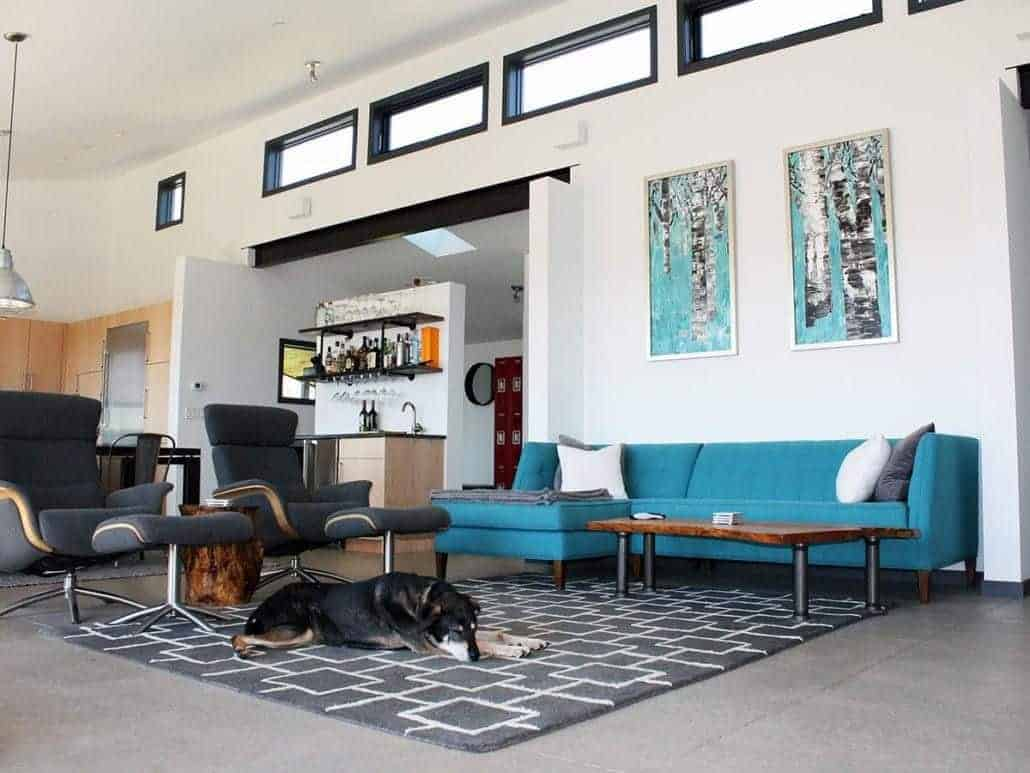 Blue artworks and sofa stand out against the white walls that are fitted with aluminum-framed windows. This room showcases black lounge chairs and a patterned rug that lays on the tiled flooring.