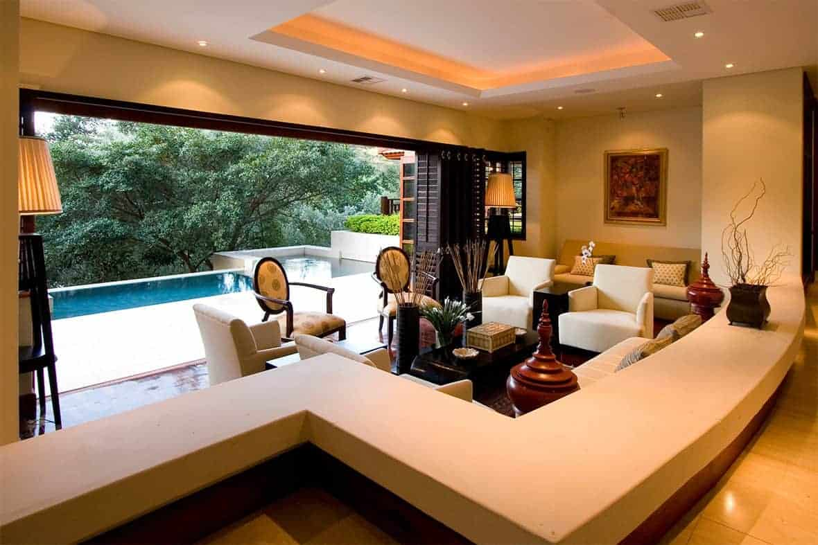 A warm living room across the swimming pool boasting a black coffee table surrounded by beige seats. It is lighted by recessed and strip lights fitted on the tray ceiling.