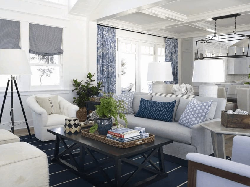 Beach style living room showcases a black coffee table and gray sofa accented with floral and chevron pillows. It has coffered ceiling and natural hardwood flooring topped by a blue striped rug.