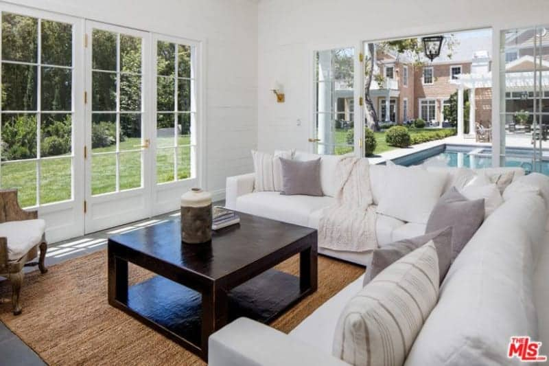 Airy living room features a white sectional sofa contrasted by a dark wood coffee table that sits on a wicker area rug. It has shiplap walls and French doors that open to the sparkling pool and lush green yard.