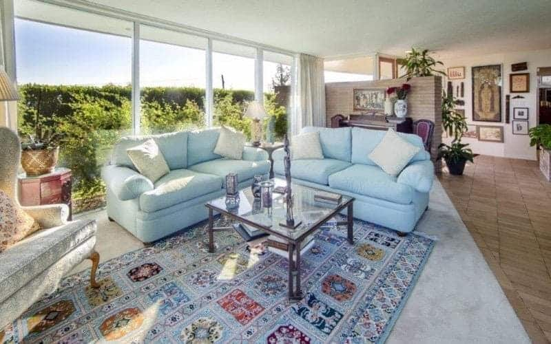 Medium-sized living area with a gray wingback seat and blue couches paired with a glass top coffee table over a printed rug. It has carpet flooring and a panoramic window overlooking the outdoor greenery.