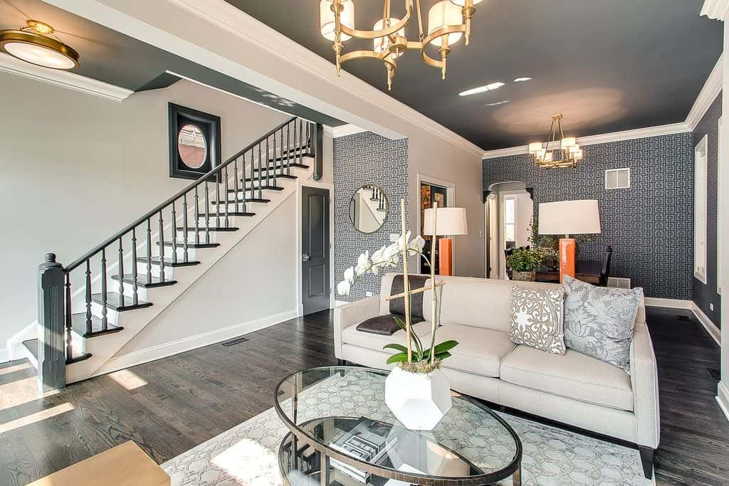 A brass chandelier illuminates this living area boasting gray sectional and an oval coffee table topped with a white geometric flower vase. It has hardwood flooring and gray walls dominated by patterned wallpaper.