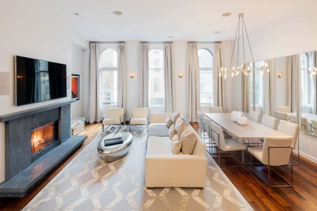 The modern living room offers a fireplace with a wall-mount TV on top along with white seats paired with a chrome coffee table over a patterned area rug. It has rich hardwood flooring and arched windows covered in gray draperies.