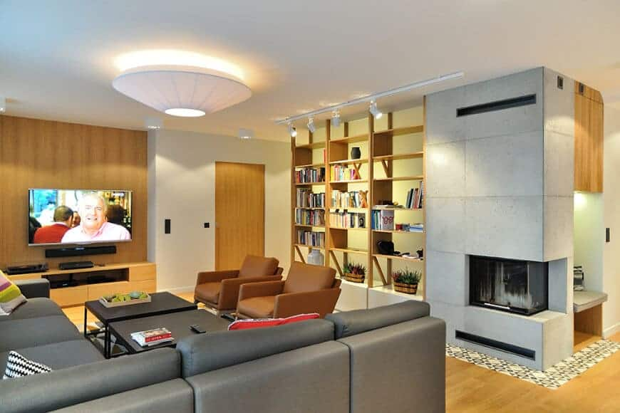 Gray sectional sofa and brown leather armchairs surround a pair of black coffee tables facing the wall mount TV that hung above the wooden console table. It is accompanied with open shelving and a modern fireplace fitted on the concrete paneled pillar.