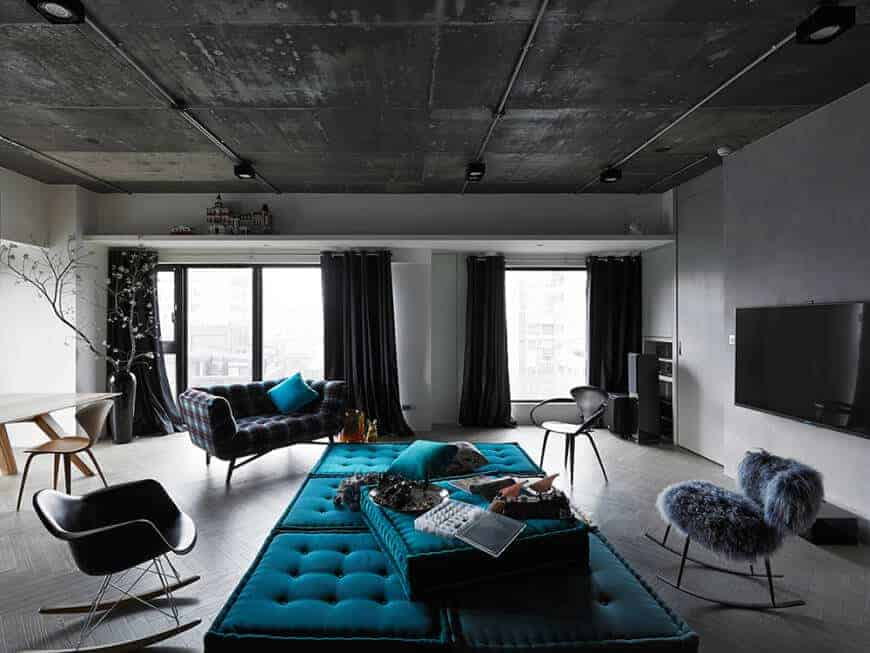 Blue pillows and tufted ottomans stand out in this black living room with mismatched chairs and a flat-screen TV mounted on the concrete wall. It has a distressed ceiling and tiled flooring arranged in a herringbone pattern.