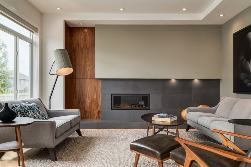 A leather lounge chair complements the round coffee table that sits on a woven area rug. This room has gray sofas and a rectangular fireplace fitted on the concrete paneled wall.