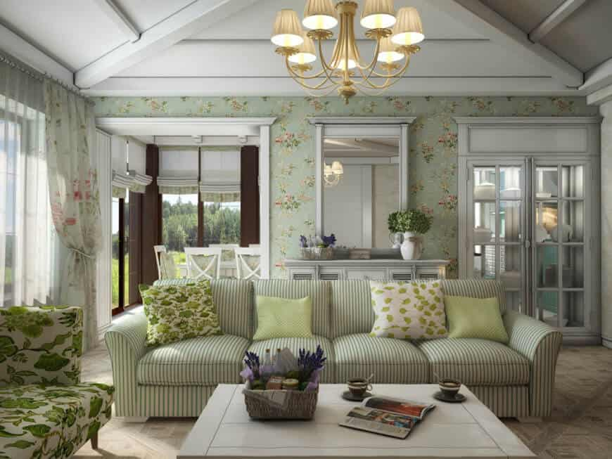 Clad in floral wallpaper, this living room showcases a striped sectional and green floral seat paired with a white coffee table. It includes brass chandelier and a framed mirror mounted above the louvered console table.