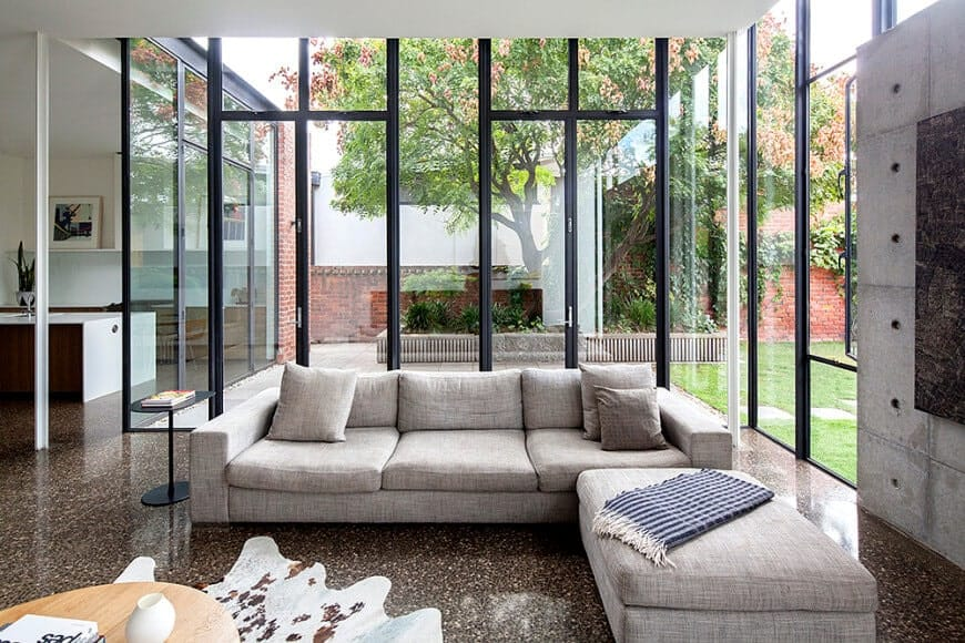 Plenty of natural light flows in through the full height glazing in this living room with a gray sectional sofa and a light wood coffee table that sits on a cowhide rug over the granite flooring.