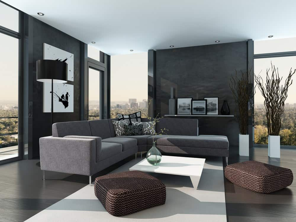 Modern living room with dark hardwood flooring and full height glazing overlooking an expansive view. It has woven ottomans and a V-shaped sectional paired with a sleek white coffee table.