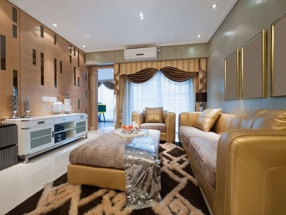 Classy living room boasts leather seats and a matching ottoman topped with a sparkling silver runner. It includes a white console table with striped storage boxes on the side against the wood paneled wall.