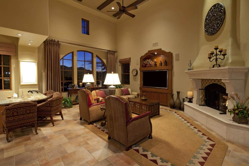 An ornate round decor hangs above the arched fireplace framed in decorative surround tiles and white mantel. This room has velvet armchairs and a striped sofa paired with a carved wood coffee table facing the wall mount TV.