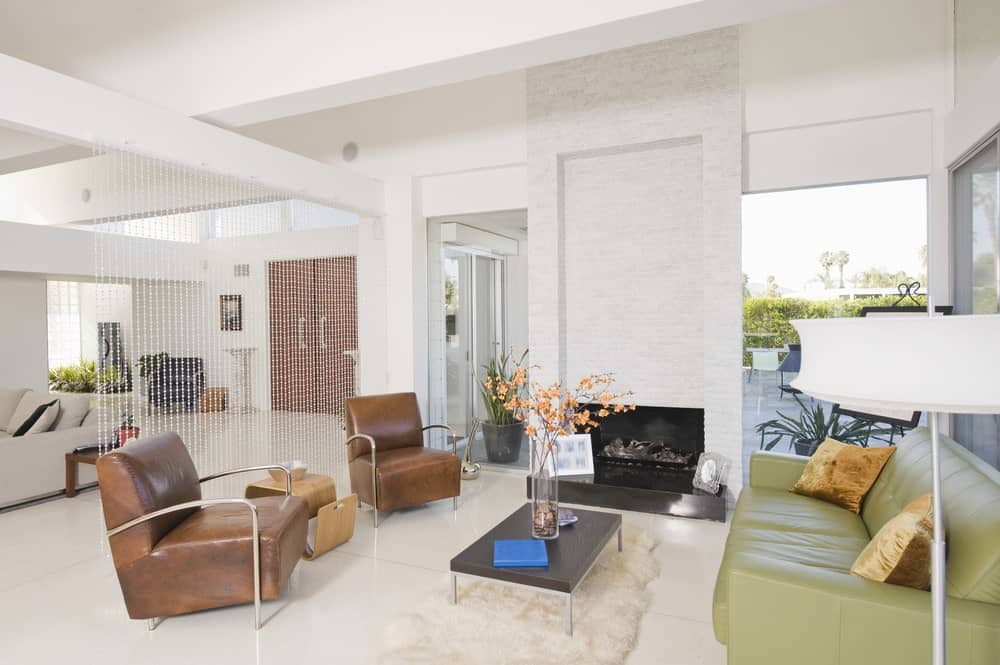 White living room with brown leather chairs and a green sofa paired with a metal coffee table that sits on a white faux fur rug. It includes an open fireplace fixed on the brick pillar.