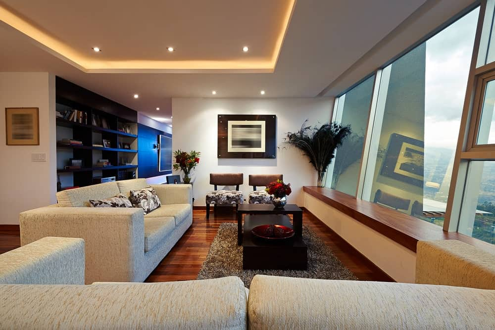 This living room offers a black coffee table over a shaggy rug along with floral cushioned chairs that match the pillows on a gray sofa. It has rich hardwood flooring and a tray ceiling mounted with recessed lights.