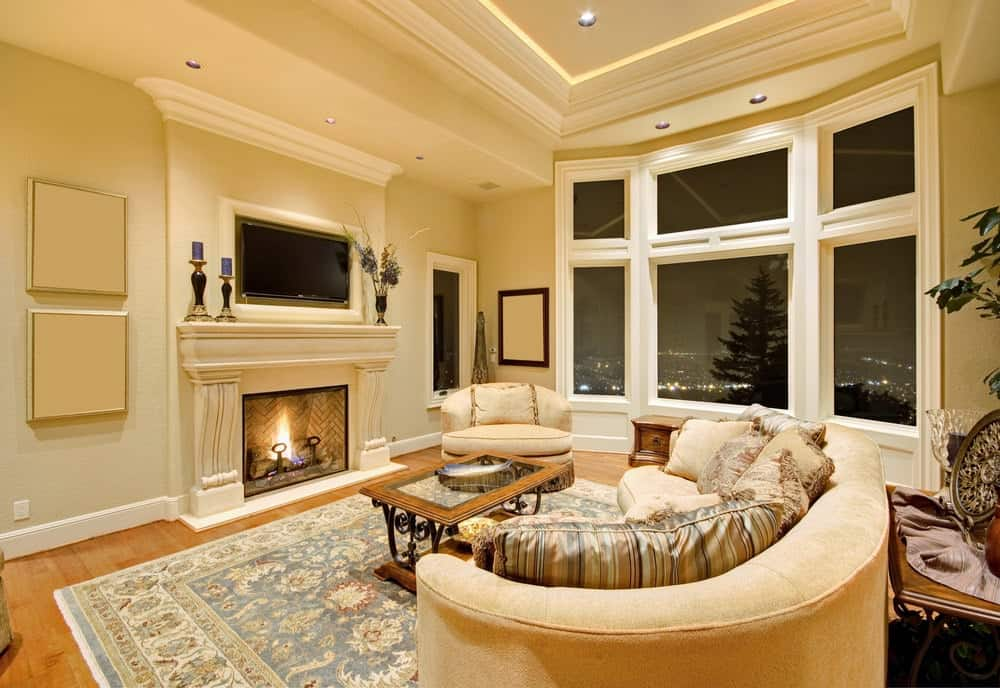 The warm living room showcases a round back chair and sofa filled with striped and beige pillows. It includes a fireplace and an ornate coffee table that sits on a blue printed rug.