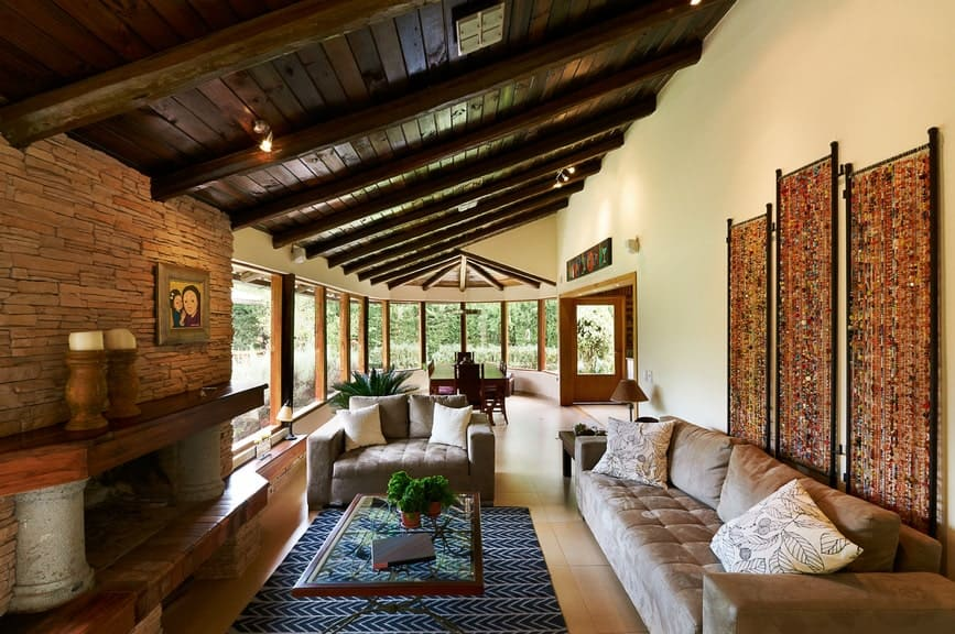 The cozy living room features gorgeous panels and a fireplace fitted on the brick accent wall. It has shed ceiling and tiled flooring topped by a blue chevron rug.