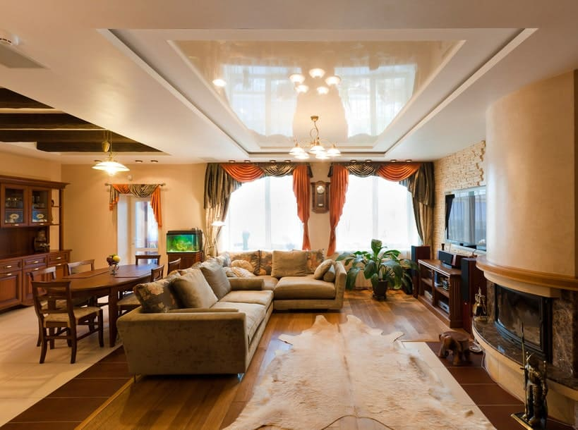 The warm living room offers a velvet sofa and a fireplace next to the wooden console table with a TV on top. It includes classy drapes and valances along with a cowhide rug that lays on the wide plank flooring.